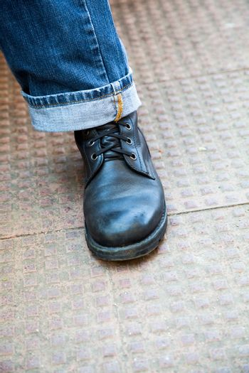 Vertical color portrait at an angle of trendy laced up leather boots and stylish turned up denim jeans on a stippled tiled ground. Generic shot of global appeal shot in Bombay India