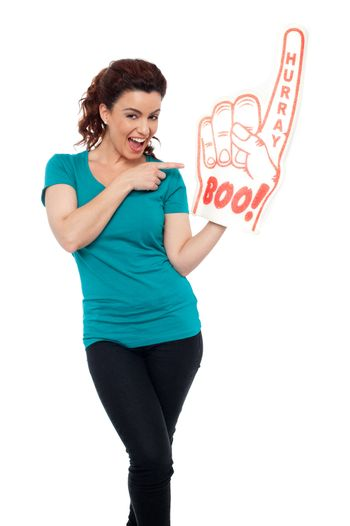 Young woman pointing at large foam hand