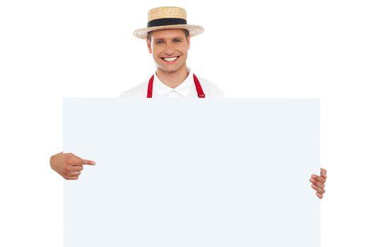 Portrait of cheerful chef pointing at placard