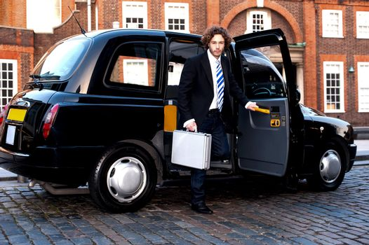 Corporate man stepping out of a cab