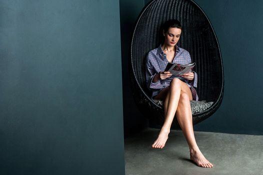 Woman reading magazine, sitting on swinging chair