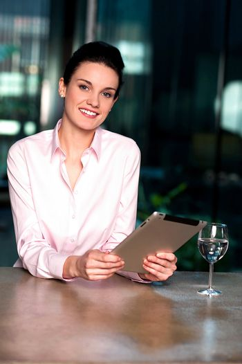 Businesswoman browsing on tablet pc with a drink beside