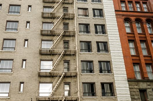 Two different color brick buildings, one with a fire escape running down the side of it in Portland, Oregon