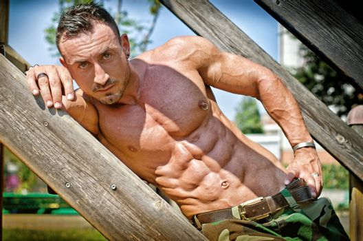 Muscular bodybuilder laying on wood stairs on a side