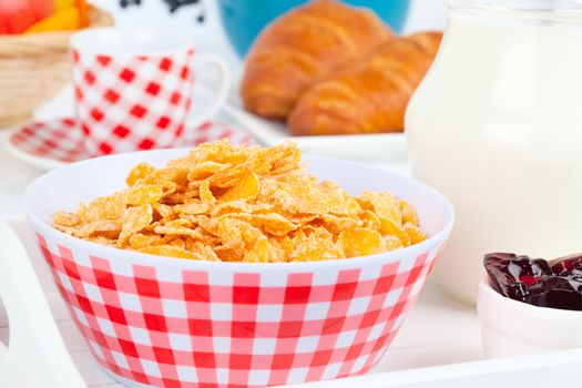Cornflakes in a porcelain bowl on table
