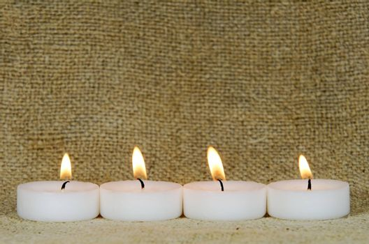 four candles on burlap background