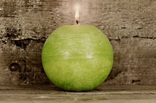 green candle on wooden background