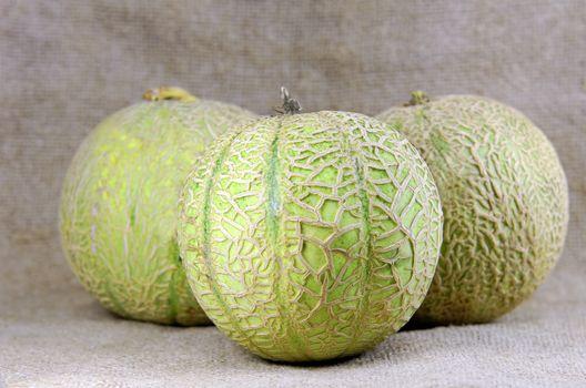 three melons on burlap background