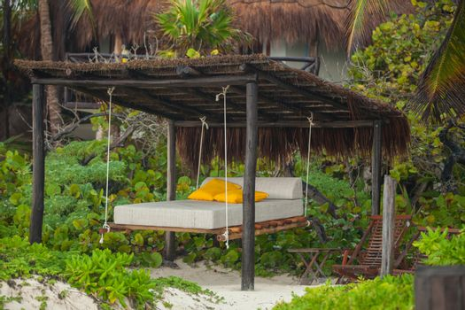 Beach beds among the trees at tropical exotic white plage