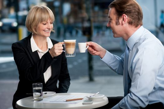 Business partners toasting coffee at cafe
