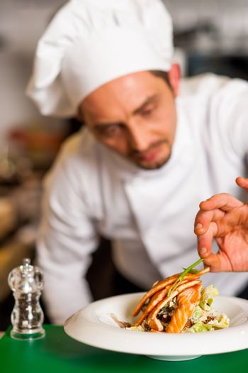 Professional chef preparing baked salmon to be served