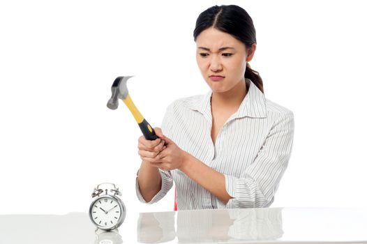 Frustrated woman smashing an alarm clock
