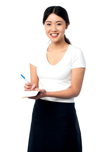 Young female assistant taking notes