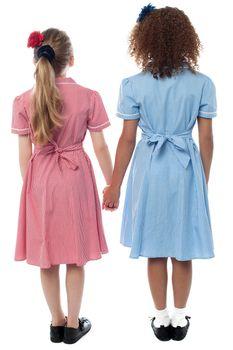 Girls in school uniform facing the wall
