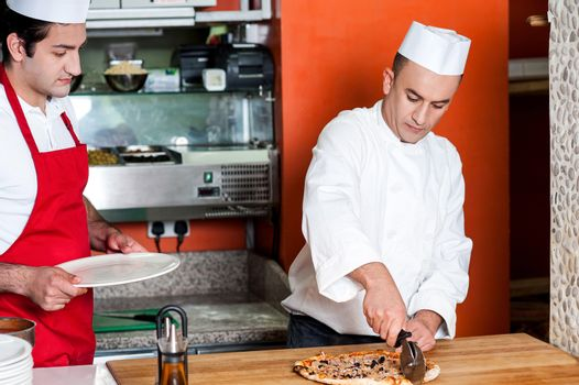 Chef cutting pizza into pieces