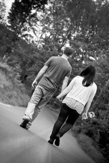 Young happy couple enjoying each others company outdoors walking down an empty road in black and white.