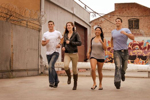 Group of friends running in urban environment.