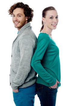 Fashion couple posing back to back