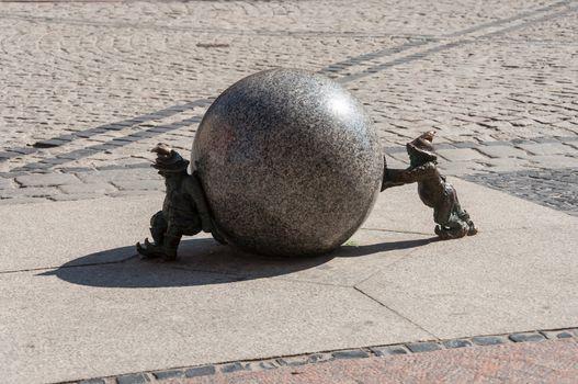 Stone dwarfs with ball on the street.