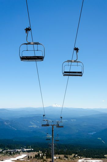 Chairlift running down Mount Hood with Mount Jefferson visible in the background