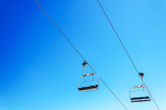 Looking up at a chairlift with a beautiful deep blue sky