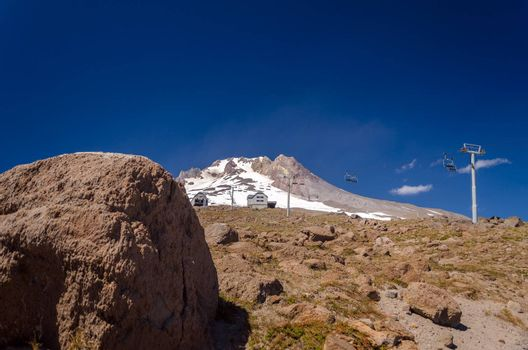 View of the summit of Mount Hood with a boulder in the foreground