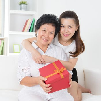 Senior woman receiving a gift from adult daughter, beautiful Asian family at home.