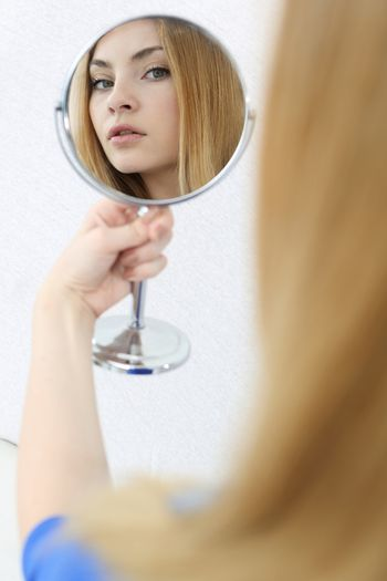 Girl looks in the mirror