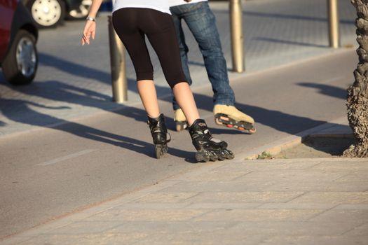 People rollerblading down a sidewalk