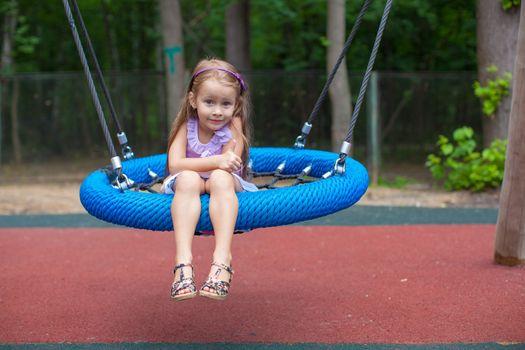 Little girl on swing at an amusement park