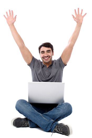 Excited young guy with laptop