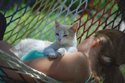 girl resting in a hammock with a kitten
