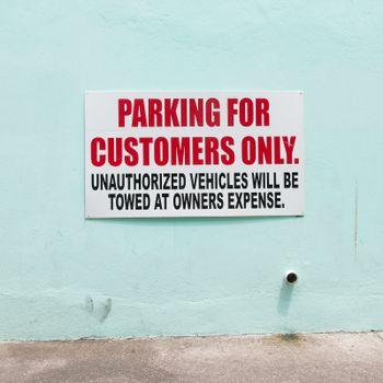 Customer parking only sign on a blue wall