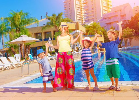 Happy family having fun near pool on luxury beach resort, sunny day, all together raised up hands, enjoying summer holidays, happiness concept