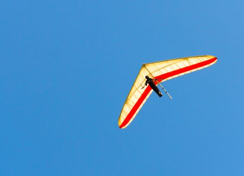 Hang Glider flying in clear blue sky
