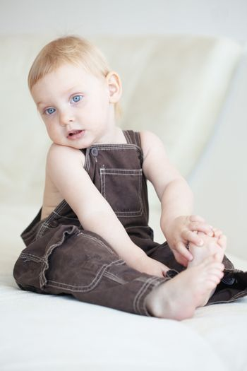 Picture of a baby sitting on a sofa at home