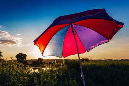 Colorful umbrella in the summer at sunset
