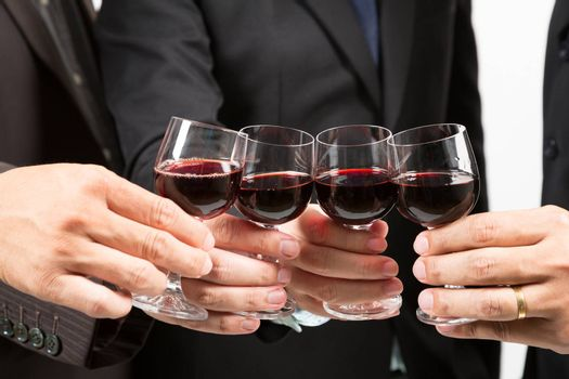 Close-up of human hands cheering up with flutes of wine