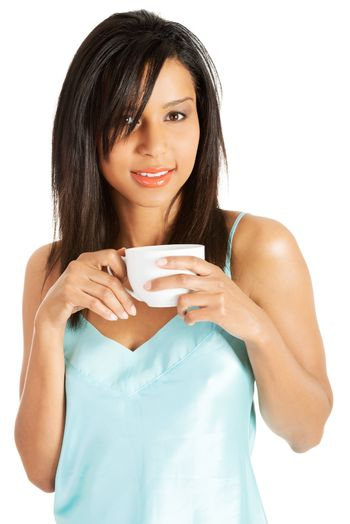 Attractive woman in nightwear drinking from cup