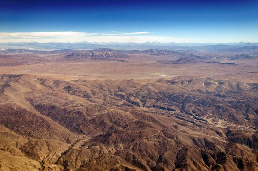 Dry desert and hills with snow capped mountains in the background somewhere over South America