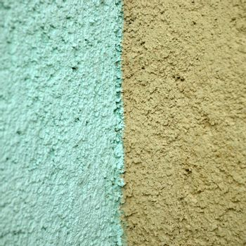 turquoise and orange stucco wall close up