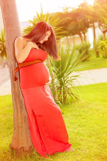 Expecting woman in summer park
