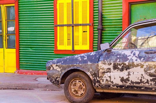 Old damaged car in front of a brightly colored building in La Boca neighborhood of Buenos Aires
