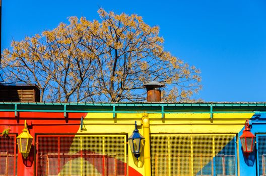 A red, yellow, and blue painted building with three lights and a beautiful blue sky in La Boca neighborhood of Buenos Aires
