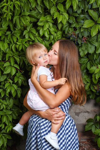 Mother holds daughter in his arms and kisses her on the cheek