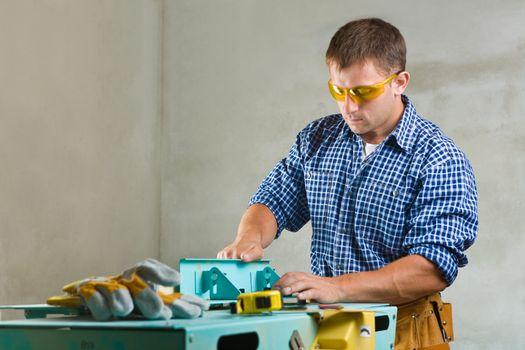 worker prepares the woodworking mashine to work
