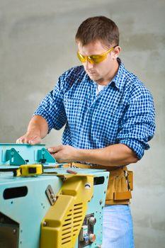 young men adjusts woodworking mashine