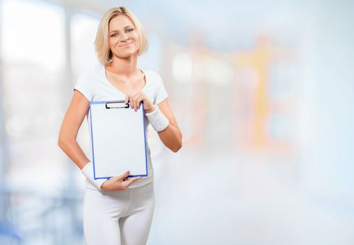 a young female in sports clothing holding clipboard