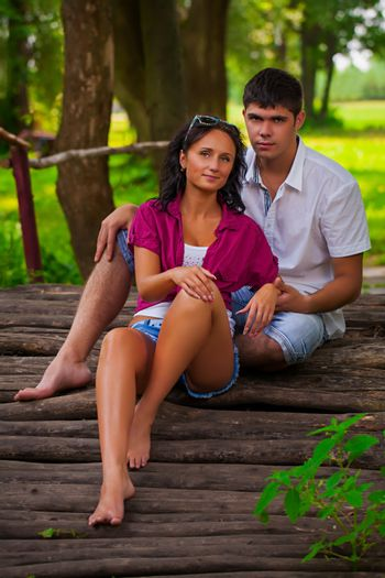 couple sitting on wooden logs