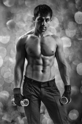 a muscular man on a background of bokeh